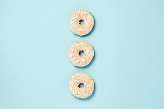 Drei frische köstliche süße donuts, die in einer reihe auf einem blauen hintergrund ausgelegt werden. fast-food-konzept, bäckerei, frühstück.