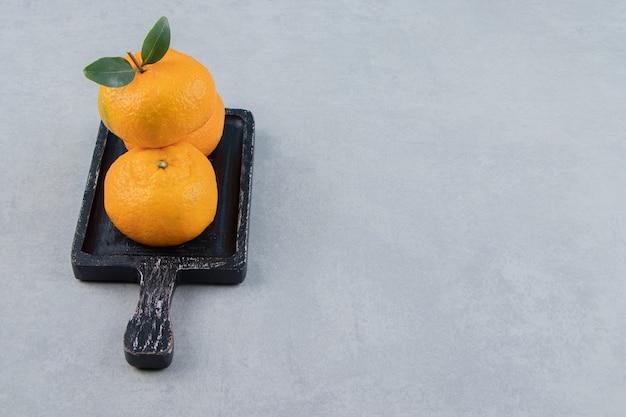 Drei frische mandarinen auf schwarzem schneidebrett