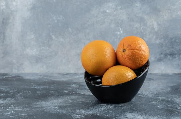 Drei frische orangen in schwarzer schüssel.