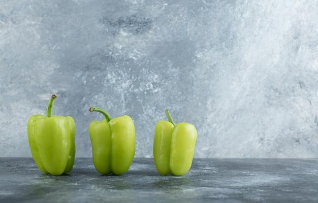 Drei frische organische gemüsepaprika auf grauem hintergrund.