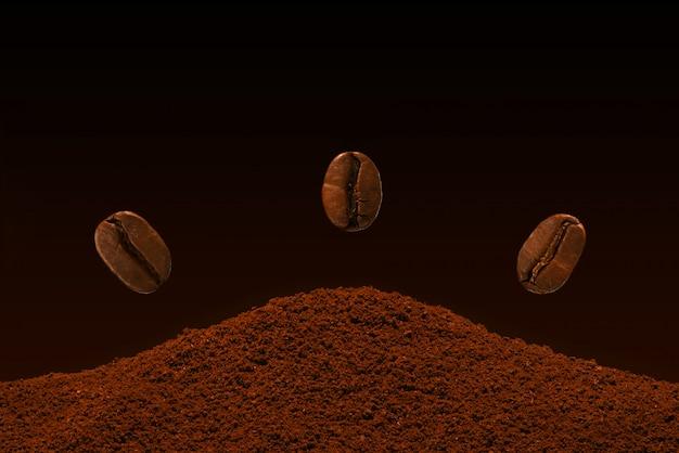 Drei frische röstkaffeebohnen fliegen über eine handvoll gemahlenen kaffee auf einem steigungshintergrund.