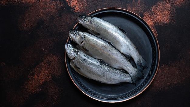 Drei frische rohe forellen auf einem weinlese-teller auf einem rustikalen dunklen hintergrund. leckere fischzutat für ein gesundes abendessen