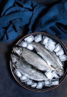 Drei frische rohe forellen in eis auf einem vintage-teller mit zitronen und meersalz auf einem dunkelblauen stoff. leckere fischzutat für ein gesundes abendessen