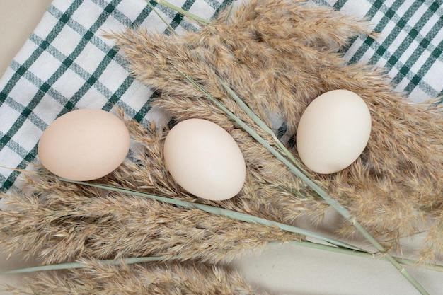 Drei frische weiße hühnereier auf tischdecke.