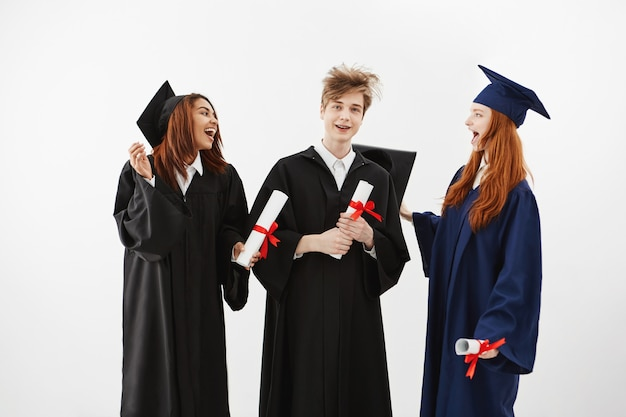 Drei fröhliche absolventen lächelnd sprechend narren halten diplome.