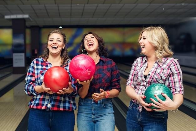 Drei fröhliche attraktive freundinnen halten bowlingkugeln und lachen.