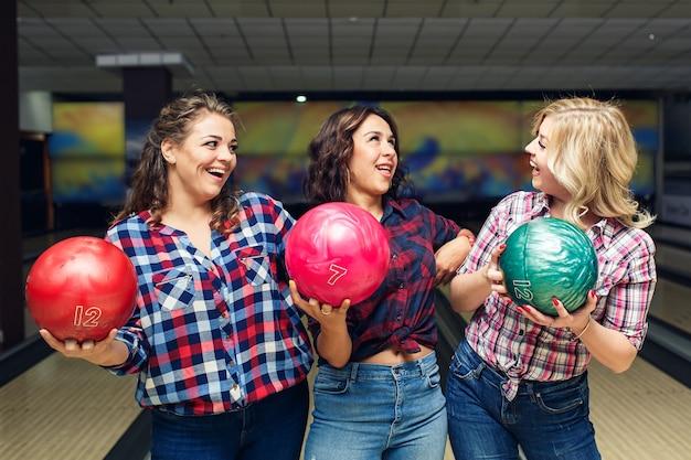 Drei fröhliche attraktive freundinnen halten bowlingkugeln und schauen sich an.
