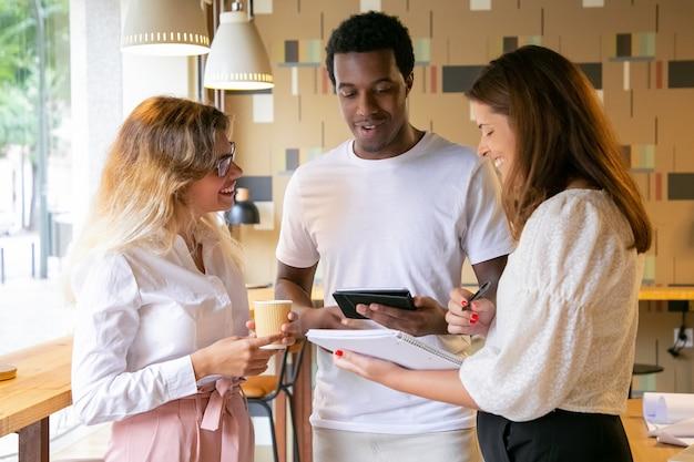 Drei fröhliche designer, die zusammen stehen, lächeln und sprechen