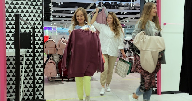 Drei fröhliche frauen gehen in die umkleidekabine eines bekleidungsgeschäfts, um verschiedene kleider anzuprobieren. schöne junge käufer in der umkleidekabine.
