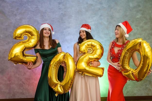 Drei fröhliche frauen mit goldenem luftballon posieren in eleganten abendkleidern. neujahr feierlichkeiten