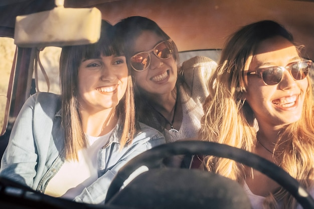 Drei fröhliche freundinnen, die im auto reisen. freundinnen, die spaß haben, während sie die autofahrt an einem hellen sommerurlaubstag genießen. freundinnen, die etwas interessantes aus dem inneren des autos bewundern