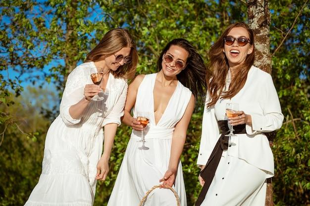 Drei fröhliche freundinnen in einem weißen kleid in der natur mit einem glas wein auf dem hintergrund der bäume an einem sommertag