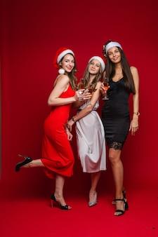 Drei fröhliche freundinnen in schönen kleidern feiern das neue jahr und freuen sich gemeinsam