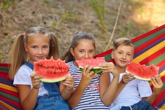 Drei fröhliche kinder essen wassermelone und witze, im freien, sitzen auf einer bunten hängematte. sommerspaß und freizeit