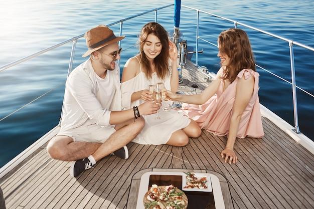 Drei fröhliche und fröhliche europäer essen an bord der yacht zu mittag, trinken champagner und verbringen eine fantastische zeit miteinander. freunde arrangierten eine überraschungsparty auf dem boot für ein b-day-mädchen