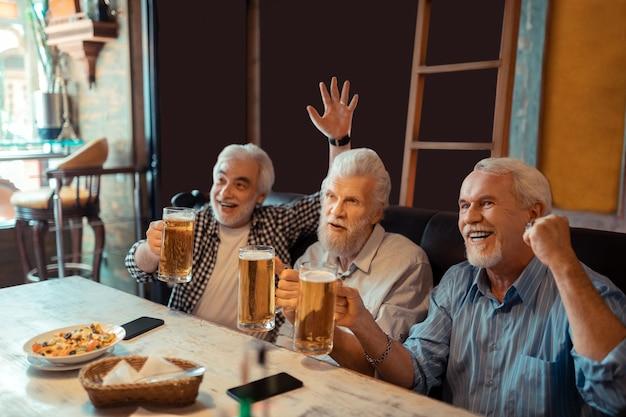 Drei fußballfans. drei fußballfans trinken bier und gucken fußball in der kneipe