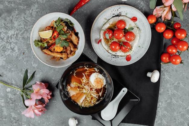 Drei-gänge-geschäftsessen. kirschtomaten mit tofu-mousse, thailändischer reis mit hühnchen und gemüse, asiatische nudelsuppe, ramen mit hühnchen.