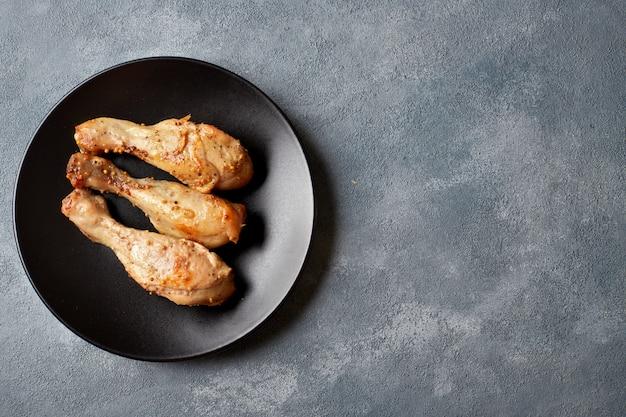 Drei gebackene hähnchenkeulen auf einem schwarzen teller