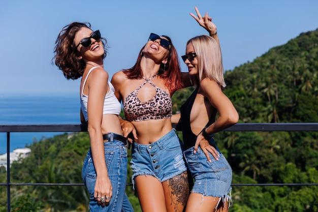 Drei gebräunte, glückliche freunde lächeln und lachen auf der terrasse