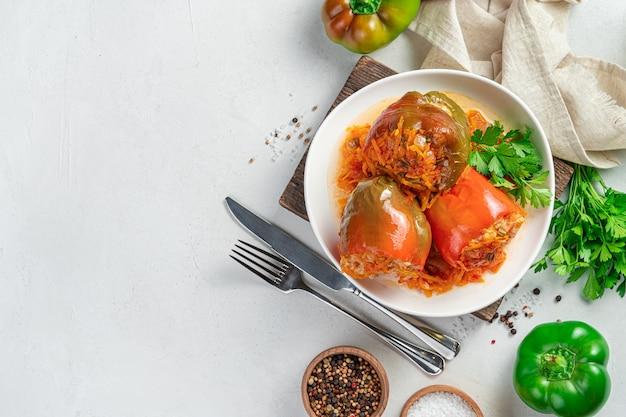 Drei gefüllte paprika mit fleischreis und gemüse auf hellem hintergrund
