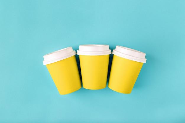 Drei gelbe einwegbecher aus papier mit geschlossenen plastikdeckeln für getränke zum mitnehmen kaffeemodell flach legen
