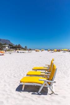 Drei gelbe liegestühle an einem sonnigen tag am sandstrand von camps bay in kapstadt