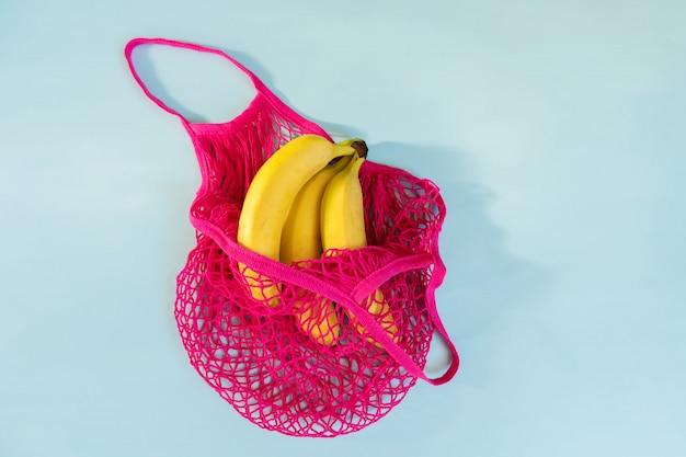 Drei gelbe reife bananen in einer pinkfarbenen eco-baumwollschnurtasche