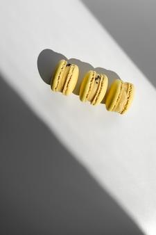 Drei gelbe zitrone französische makronen oder macarons nachtisch auf weißem hintergrund mit lichtstrahlen vom fenster.
