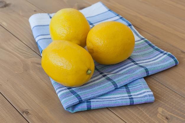Drei gelbe zitronen auf einer leicht karierten serviette