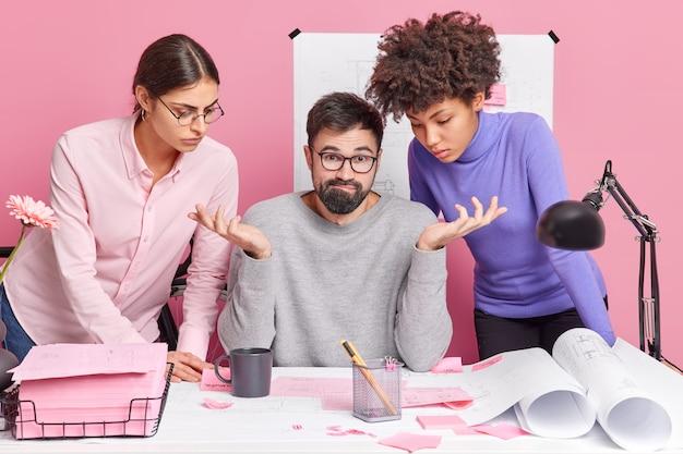 Drei gemischte büroingenieure arbeiten für gemeinsame projektarbeit an der blaupausenpose in modernen arbeitsbereichen zusammen und versuchen, eine lösung zu finden, die zögernd aussieht brainstorming teamarbeit und kooperationskonzept