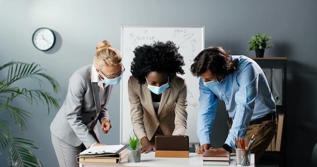 Drei gemischte rassen männer und frauen in medizinischer maske stehen im büro und beobachten etwas auf dem smartphone. multiethnische lehrer diskutieren über das online-konzept des lernens per handy. mann und frauen.