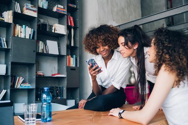 Drei gemischtrassige junge frauen, die den smartphone im modernen büro mitarbeiten schauen