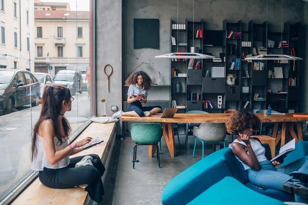Drei gemischtrassige junge geschäftsfrauen, die in modernem coworking büro arbeiten