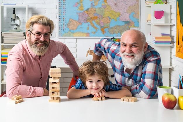 Drei generationen aktiver männer, die zu hause im wohnzimmer-jenga-spiel spielen