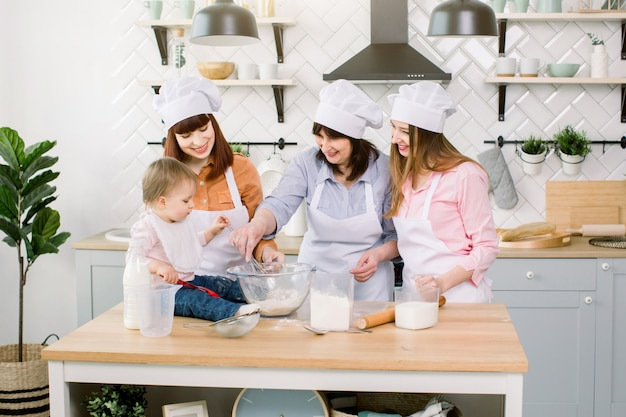 Drei generationen von frauen in weißen schürzen spielen und lachen, während sie den teig in der küche kneten, mehl mit eiern mischen und teig in einer modernen küche zubereiten