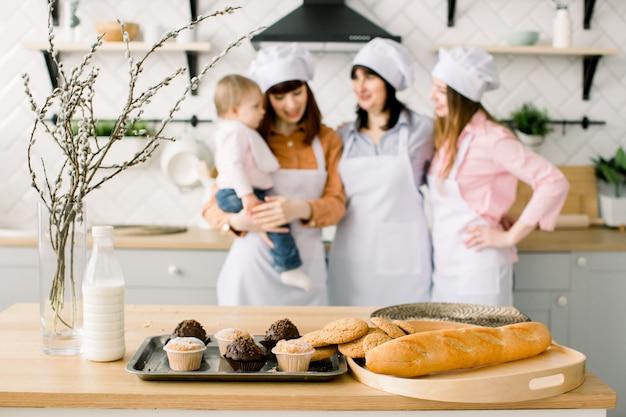 Drei generationen von frauen kochen in der küche, konzentrieren sich mit maffinen und keksen auf den tisch. hausgemachtes essen und kleiner helfer. glückliche familie. backen in der küche. osterferien oder muttertag
