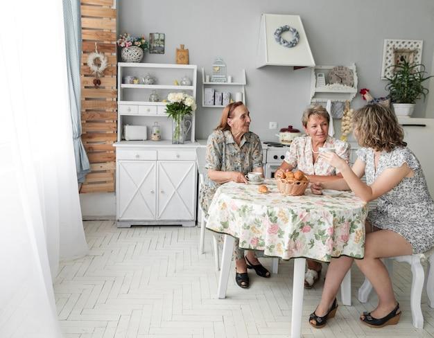 Drei generationsfrauen, die etwas während des frühstücks besprechen