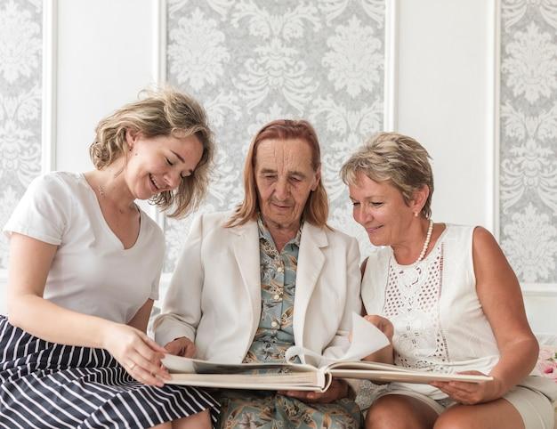 Drei generationsfrauen, die fotoalbum beim sitzen auf sofa schauen
