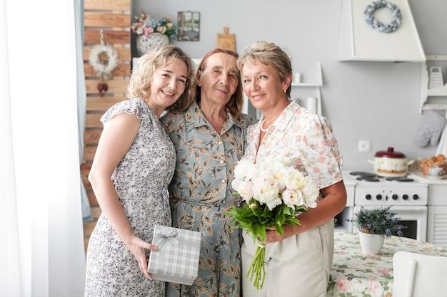 Drei generationsfrauen, die zusammen stehen, blumenblumenstrauß und -geschenk halten, die kamera betrachten