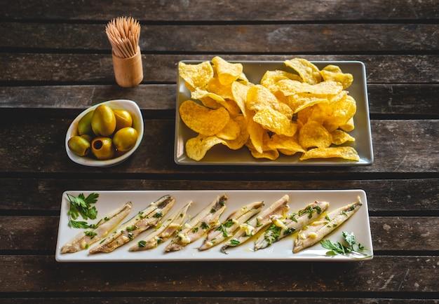Drei gerichte mit kartoffelchips, gepflückten sardellen und grünen oliven auf einem dunklen holztisch mit zahnstochern. typische spanische snacks.