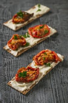 Drei geröstete brote mit frischkäse und sonnengetrockneten tomaten auf einem holztisch. vegetarischer snack aus hüttenkäse und tomaten.