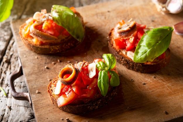 Drei geröstete tomatenbruschetta mit tomaten olivenöl sardellen oregano und basilikum
