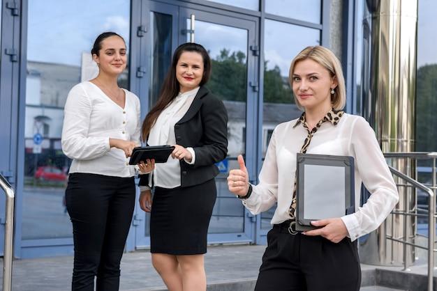 Drei geschäftsdamen mit tabletten, die außerhalb des gebäudes stehen und in die kamera schauen