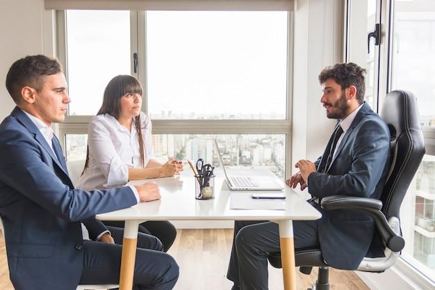Drei geschäftsfachleute, die im büro zusammenarbeiten