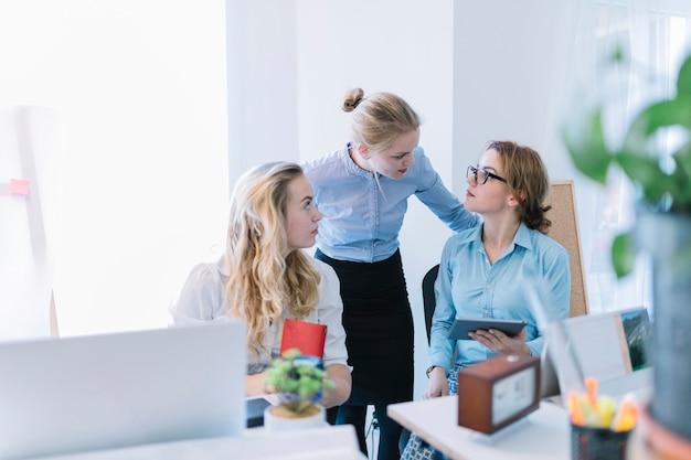 Drei geschäftsfrauen, die gespräch im büro haben