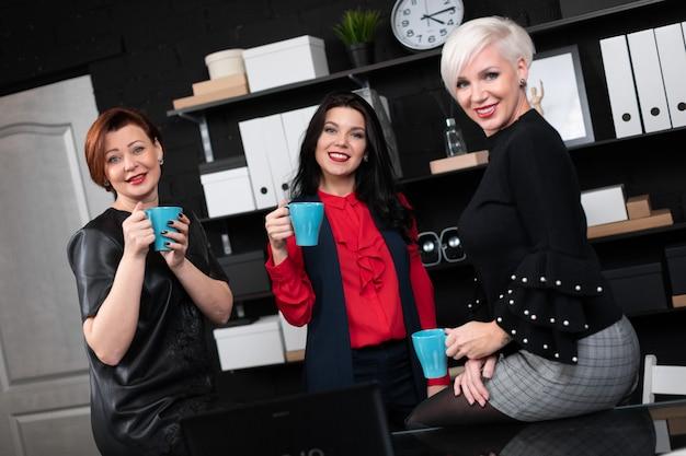 Drei geschäftsfrauen, die in der hand mit kaffee im stilvollen büro sprechen