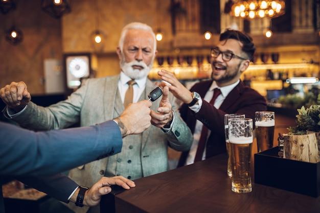Drei geschäftsleute feiern erfolgreich erledigte arbeit im restaurant. ein mann nimmt seinem betrunkenen geschäftspartner den autoschlüssel ab.