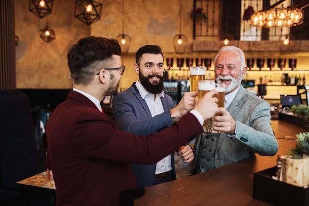 Drei geschäftsleute feiern erfolgreich erledigte arbeit im restaurant. Premium Fotos