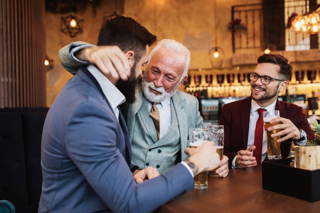 Drei geschäftsleute feiern erfolgreich erledigte arbeit im restaurant.