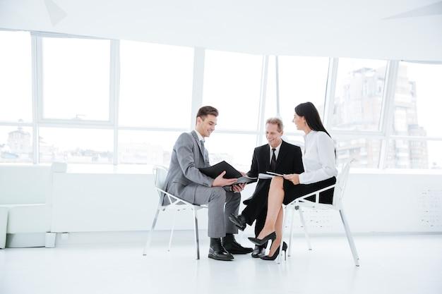 Drei geschäftsleute in voller länge sitzen auf stühlen mit dokumenten im büro